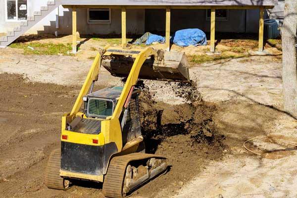 bobcat mini excavator clearning soil from backyard