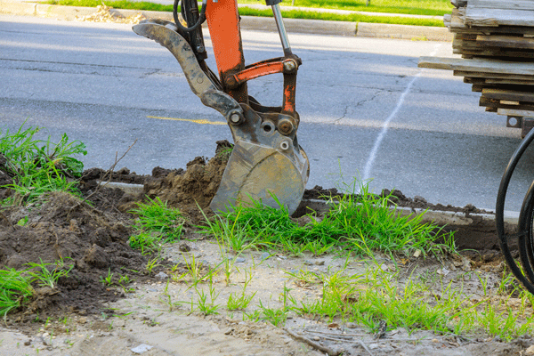 excavator performing trenching for drainage pipe laying