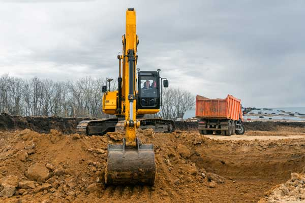 large excavator performing soil removal drainage work