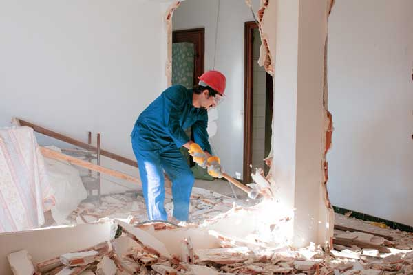 man working on small building demolition
