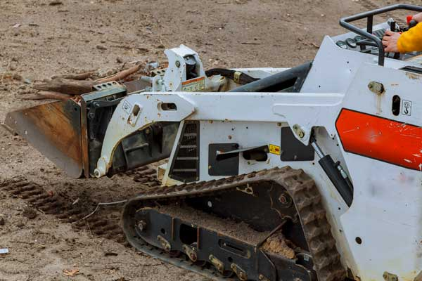 white mini excavator performing earthmoving